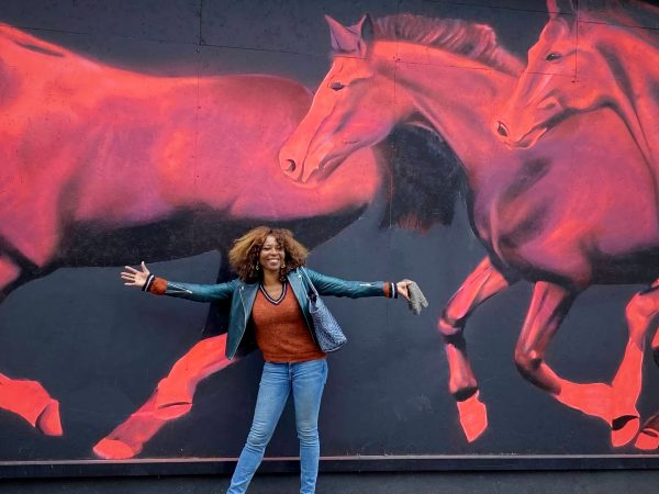 Valerie Brown, London Mayoral Candidate standing in front of Pink Horses Mural